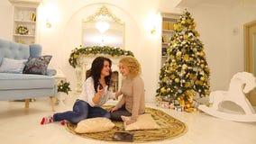 De blije en leuke meisjes babbelen en gebruiken gadget, zittend op vloer op achtergrond van open haard en Kerstboom in het grote  stock videobeelden