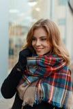 De blije gelukkige jonge vrouw in een modieuze warme wolsjaal in een modieuze zwarte laag in zwarte handschoenen bevindt zich en  royalty-vrije stock afbeeldingen