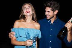 De blije glazen van de paarholding en fles champagne bij nacht Royalty-vrije Stock Fotografie