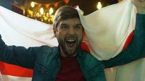 De blije golvende vlag van de sportenventilator van Engeland in bar, verheugende favoriete teamoverwinning stock videobeelden