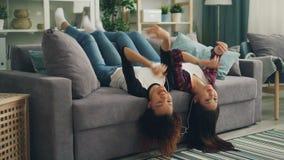 De blije jonge dames hebben pret samen thuis luisterend aan muziek met zich smartphone en oortelefoons en het dansen het bewegen stock video