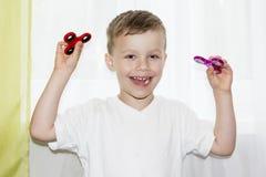 De blije jongen glimlacht thuis en houdt in zijn hand twee spinners Kind het spelen met twee friemelt spinners royalty-vrije stock afbeelding