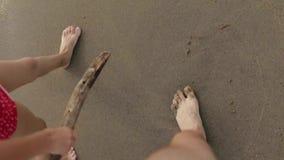 De blije jongen van de Europese verschijning gaat naar het strand met een stok in hand met papa De camera neemt de benen en stock footage