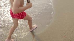 De blije jongen van de Europese verschijning gaat naar het strand met een stok in zijn handen De camera neemt de benen en het gez stock video