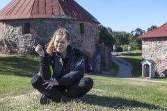 De blije Kaukasische vrouw in motorfietsjasje, knie bewaakt het zitten op groene weide in één of ander oriëntatiepunt, copyspace royalty-vrije stock afbeelding