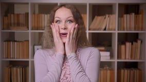De blije Kaukasische wavy-haired rollende ogen die van de blondeleraar uiterst bij bibliotheek worden geamuseerd en worden verras stock footage