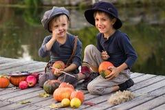 De blije kinderen schilderen kleine Halloween-pompoenen Royalty-vrije Stock Afbeelding