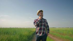 De blije landbouwer in strohoed en het geruite overhemd die op een cel spreken telefoneren met gelukkige emoties tijdens het lope stock video