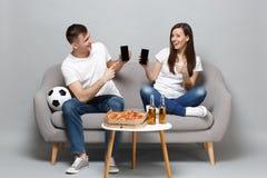 De blije de man van de paarvrouw voetbalfans juichen steun omhoog favoriet team toe, die mobiele telefoon met het lege lege scher stock fotografie