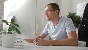 De blije mens werkt in bureau bij computer en communiceert stock video