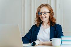 De blije mooie vrouw heeft gemberhaar, positieve glimlach, zit met laptop computer bij Desktop, gelukkig om videogesprek of confe stock fotografie