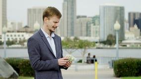 De blije rijke man telt zijn geld op een straat stock footage