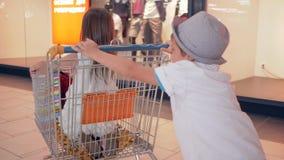 De blije rit van het vriendenkind in het winkelen karretjes bij wandelgalerij voorbij winkelvensters van boutique stock video
