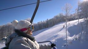 De blije snowboardervrouw neemt op de lift toe tot de bovenkant van de berg stock videobeelden