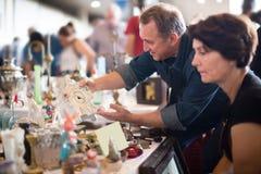 De blije toeristen bestuderen de waaier van vlooienmarkt stock afbeeldingen