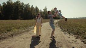 De blije vader raapt zijn zoon op en roteert hem stock video