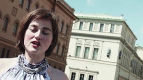 De blije vocalistvrouw presteert in oude stad in de zomerkleding stock videobeelden