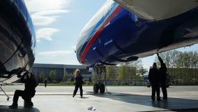 De blije vrouw danst dichtbij vliegtuigen vast door technici stock videobeelden