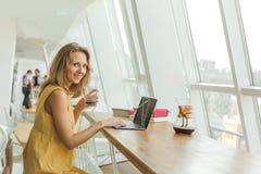 De blije vrouw drinkt koffie en het werken royalty-vrije stock fotografie