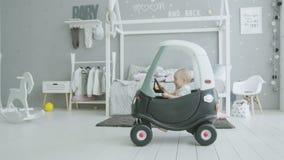 De blije zitting van het zuigelingsmeisje in miniatuurauto thuis stock videobeelden