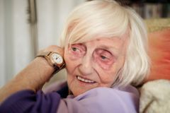 De blinde oude vrouw luistert aan de tijd op haar het spreken polshorloge stock foto