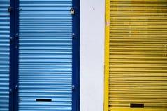 De blinden van winkels sloten geel en blauw stock afbeelding