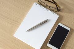 De blocnote, smartphone, de glazen en de strook ballpen stock foto's