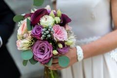 De bloem die van het huwelijksboeket jonge vrouw houden Stock Afbeelding