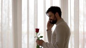 De bloem en de telefoon van de mensenholding stock video