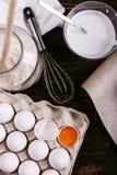 De bloem, kefir eieren en zwaait op een houten lijst Het voorbereiden van het mengsel voor pannekoeken, het koken stock fotografie