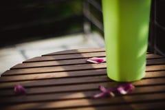 De bloemblaadjes van een roze tulp ligt op een houten lijst dichtbij groene vaas op zon stock fotografie