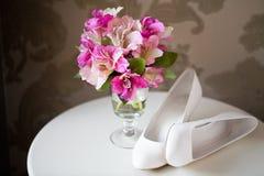 De bloemen en de schoenen van het huwelijk stock afbeelding