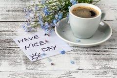 De bloemen van de vergeet-mij-nietjelente en kop van koffie op houten plattelander Stock Foto