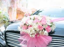 De bloemen van het huwelijksboeket op luxe zwarte auto Stock Fotografie