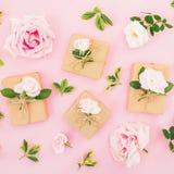 De bloemendiesamenstelling van rozenbloemen wordt gemaakt en de giftdozen op pastelkleur doorboren achtergrond Vlak leg, hoogste  royalty-vrije stock foto