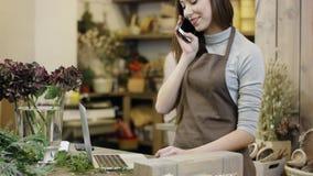 De bloemenkunstenaar die iets op haar laptop typen en beantwoordt het telefoongesprek, gaat de camera van bodem tot de bovenkant stock videobeelden