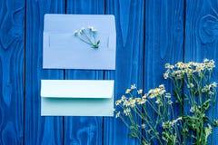 De bloemensamenstelling met kamille en prentbriefkaarenveloppen op blauwe houten vlakte als achtergrond legt model Stock Foto