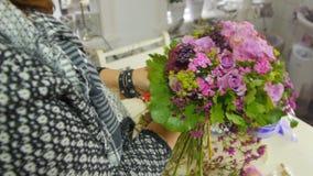 De bloemist brengt een boeket van bloemen samen stock video