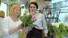 De bloemist en de medewerker creëren bloemboeket met rozen en tulpen stock video
