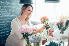 De bloemist neemt een bloem om een boeket te maken Royalty-vrije Stock Foto's