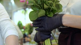De bloemist toont medewerker hoe te om bloemboeket te creëren stock footage