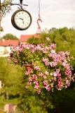 De bloemmand met rode en witte bloemen en de bruine uitstekende muur zetten klok op Royalty-vrije Stock Fotografie