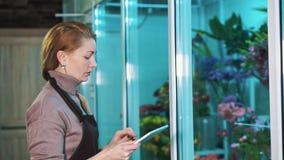 De de bloemwinkel van de vrouwenmaitresse telt het aantal goederen en schrijft aan de tablet stock video