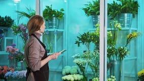 De de bloemwinkel van de vrouwenmaitresse telt het aantal goederen en schrijft aan de tablet stock videobeelden