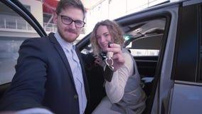 De Bloggerskerel met meisje met sleutels registreert video in levende uitzending op mobiele telefoon dichtbij nieuwe gekochte aut stock video