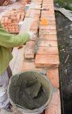 De Blokken van metselaarsworker installing red en Waterdicht makende de Verbindingen Buitenmuur van het Baksteenmetselwerk met he stock fotografie