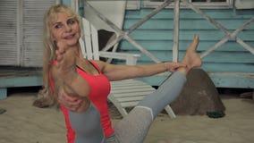De blonde dame heeft yoga buiten opleiding, dichtbij het blauwe huis stock footage