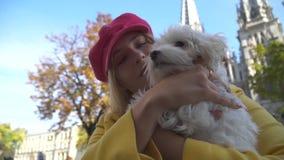 De blonde dame kust haar hond bij de stad stock videobeelden