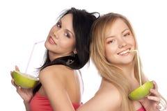 De blonde en de brunette drinken sap van citrusvrucht stock foto