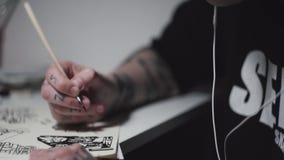 De blonde getatoeeerde tekening van de kunstenaars punkvrouw bij bureau in lamplicht stock footage